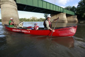 Geoff and Pamela MacDonald with son, Jude, and Taq pull away from The Forks to continue their journey across Canada Sunday. They have paddled 7,000 km.